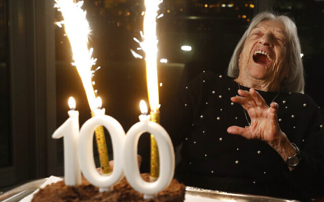 Agnes Keleti, former Olympic gold medal winning gymnast, reacts to fireworks going off on her birthday cake in Budapest, Hungary Monday Jan. 4, 2021. The oldest living Olympic champion turns 100 and says the fondest memory of her remarkable life is simply that she has lived through it all. Keleti had her illustrious career interrupted by World War II and the subsequent cancellation of the 1940 and 1944 Olympics. (AP Photo/Laszlo Balogh)